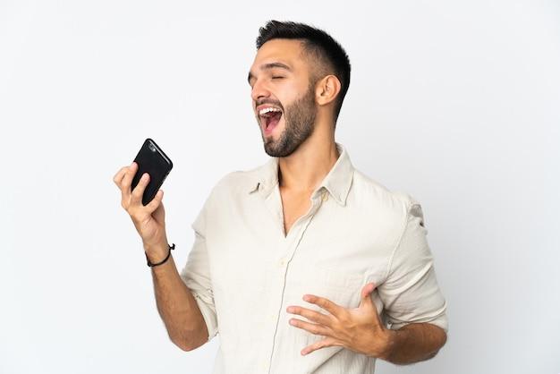 Jovem homem caucasiano isolado no fundo branco usando telefone celular e cantando
