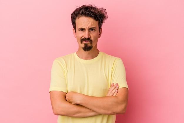 Jovem homem caucasiano isolado no fundo rosa, rosto carrancudo em desgosto, mantém os braços cruzados.
