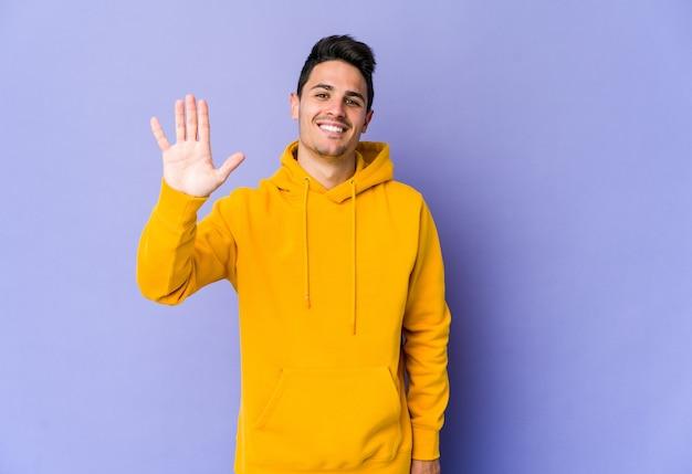 Jovem homem caucasiano isolado no fundo roxo, sorrindo alegre mostrando o número cinco com os dedos.