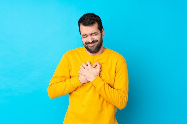 Jovem homem caucasiano isolado parede azul com uma dor no coração