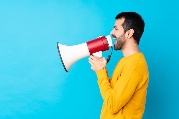 Jovem homem caucasiano isolado parede azul gritando através de um megafone