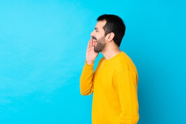 Jovem homem caucasiano isolado parede azul gritando com a boca aberta para a lateral