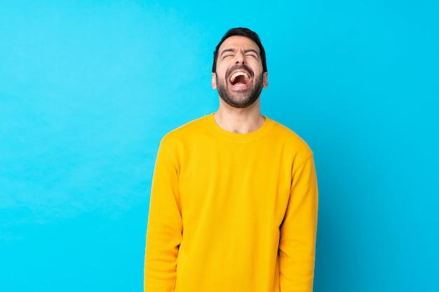 Jovem homem caucasiano isolado parede azul gritando para a frente com a boca aberta