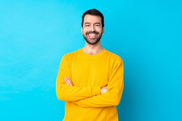 Jovem homem caucasiano isolado parede azul, mantendo os braços cruzados na posição frontal