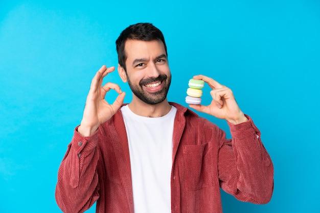 Jovem homem caucasiano isolado parede azul segurando macarons franceses coloridos e mostrando sinal de ok com os dedos