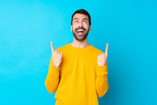 Jovem homem caucasiano isolado parede azul surpreso e apontando para cima