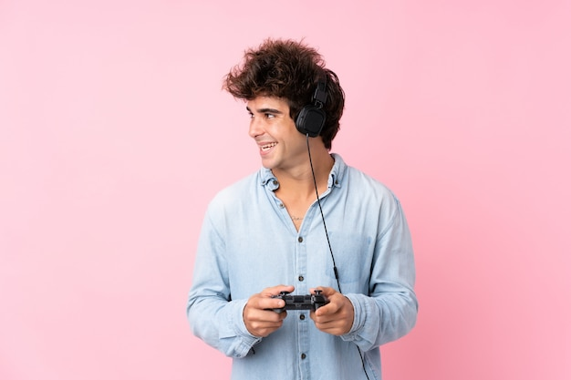 Jovem homem caucasiano isolado parede rosa jogando em videogame