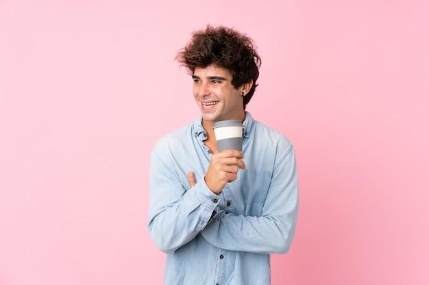 Jovem homem caucasiano isolado parede rosa segurando café para tirar