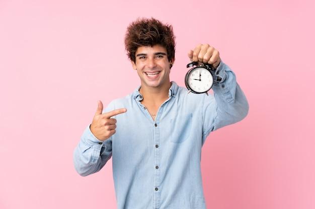 Jovem homem caucasiano isolado parede rosa segurando despertador vintage
