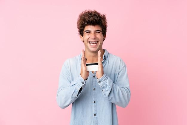 Jovem homem caucasiano isolado parede rosa segurando um cartão de crédito