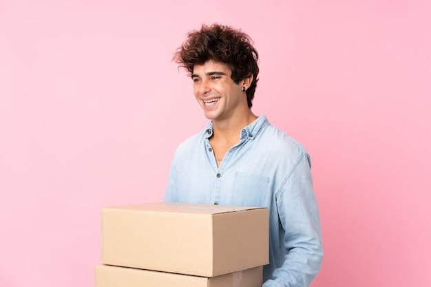 Jovem homem caucasiano isolado parede rosa segurando uma caixa para movê-lo para outro site