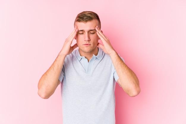 Jovem homem caucasiano isolado tocando os templos e tendo dor de cabeça.
