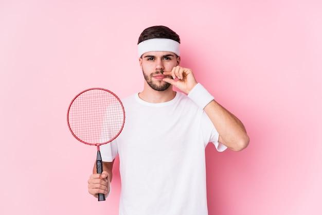 Jovem homem caucasiano jogando badminton isolado com os dedos nos lábios, mantendo um segredo.