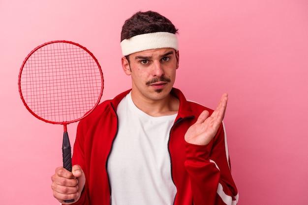 Jovem homem caucasiano jogando badminton isolado no fundo rosa surpreso e chocado.