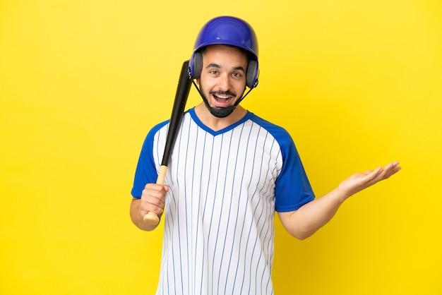 Jovem homem caucasiano jogando beisebol isolado em um fundo amarelo com expressão facial chocada
