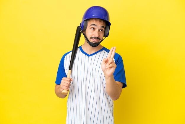 Jovem homem caucasiano jogando beisebol isolado em um fundo amarelo, cruzando os dedos e desejando o melhor