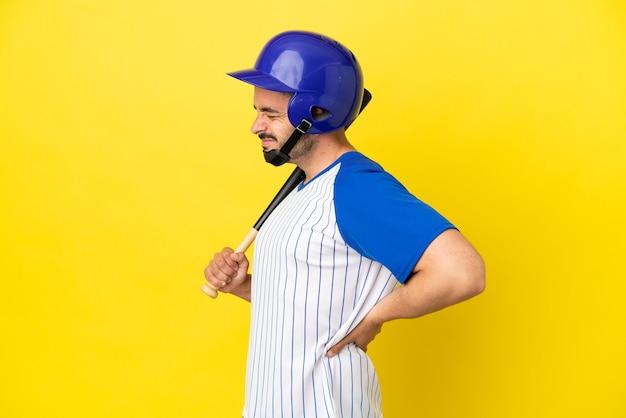 Jovem homem caucasiano jogando beisebol isolado em um fundo amarelo, sofrendo de dor nas costas por ter feito um esforço