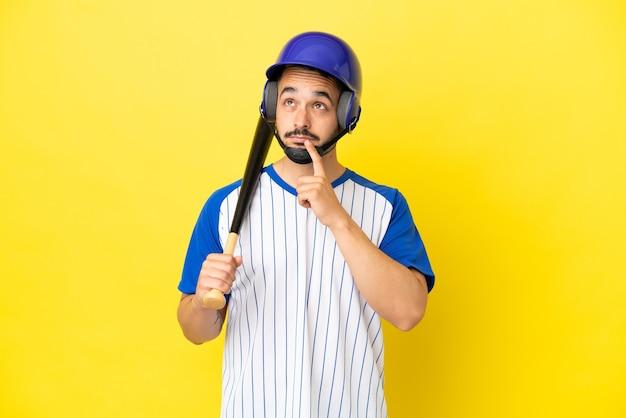 Jovem homem caucasiano jogando beisebol isolado em um fundo amarelo, tendo dúvidas enquanto olha para cima