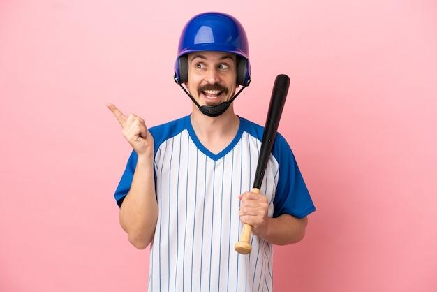 Jovem homem caucasiano jogando beisebol isolado em um fundo rosa com a intenção de descobrir a solução enquanto levanta um dedo
