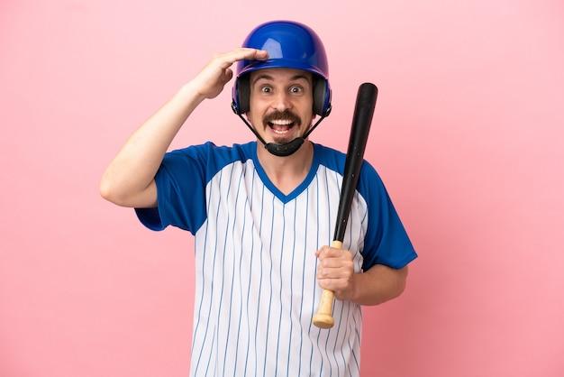 Jovem homem caucasiano jogando beisebol isolado em um fundo rosa com expressão de surpresa