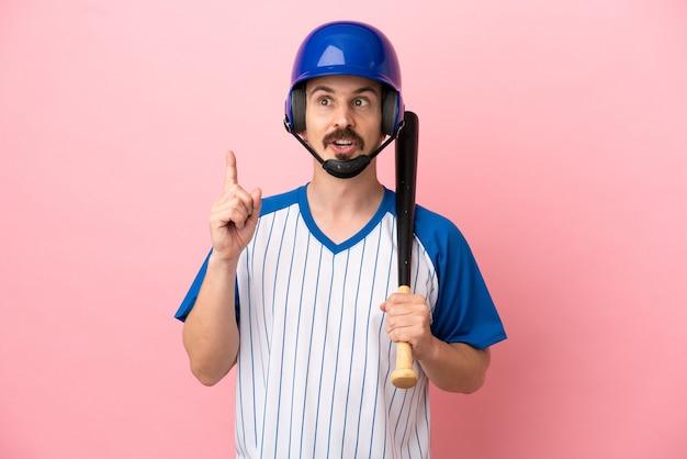 Jovem homem caucasiano jogando beisebol isolado em um fundo rosa pensando em uma ideia apontando o dedo para cima