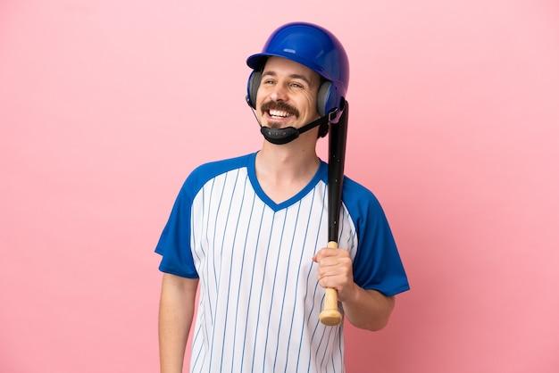 Jovem homem caucasiano jogando beisebol isolado em um fundo rosa pensando em uma ideia enquanto olha para cima
