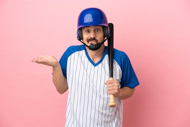 Jovem homem caucasiano jogando beisebol isolado em um fundo rosa, tendo dúvidas ao levantar as mãos