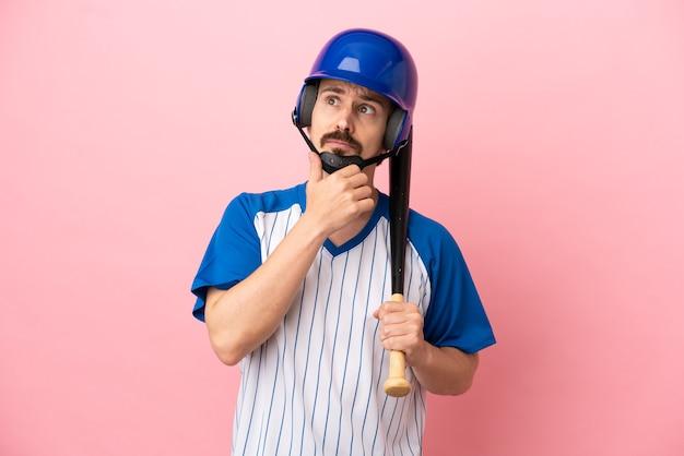 Jovem homem caucasiano jogando beisebol isolado em um fundo rosa, tendo dúvidas