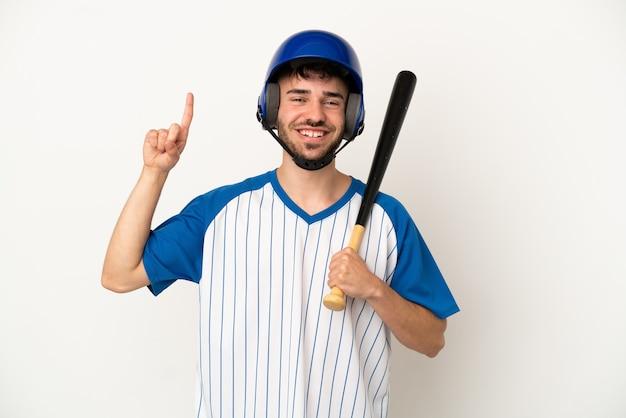 Jovem homem caucasiano jogando beisebol isolado no fundo branco apontando uma ótima ideia