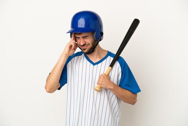 Jovem homem caucasiano jogando beisebol isolado no fundo branco com dor de cabeça