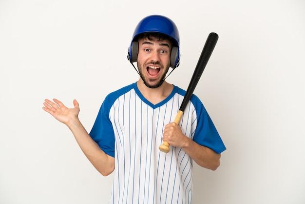 Jovem homem caucasiano jogando beisebol isolado no fundo branco com expressão facial chocada