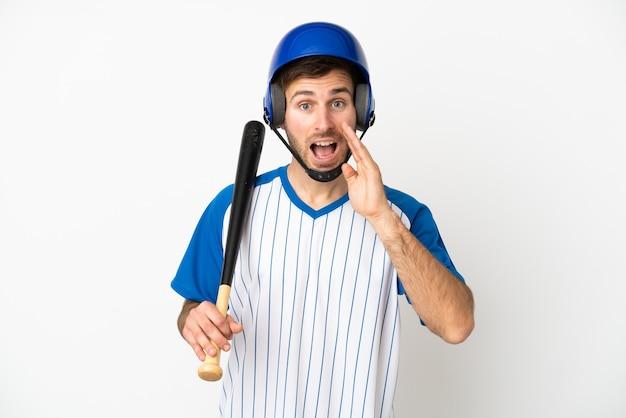 Jovem homem caucasiano jogando beisebol isolado no fundo branco com expressão facial de surpresa e choque