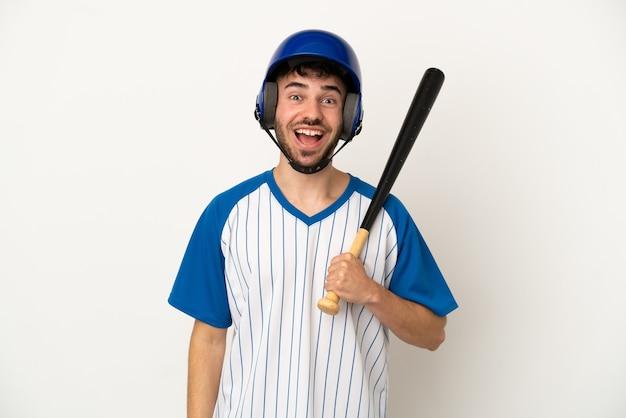 Jovem homem caucasiano jogando beisebol isolado no fundo branco com expressão facial surpresa