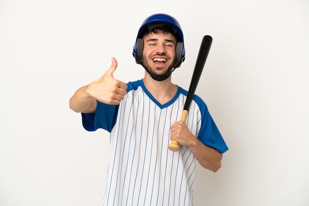 Jovem homem caucasiano jogando beisebol isolado no fundo branco com o polegar para cima porque algo bom aconteceu