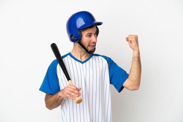Jovem homem caucasiano jogando beisebol isolado no fundo branco comemorando uma vitória