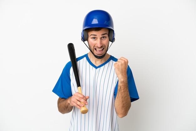 Jovem homem caucasiano jogando beisebol isolado no fundo branco e comemorando a vitória na posição de vencedor