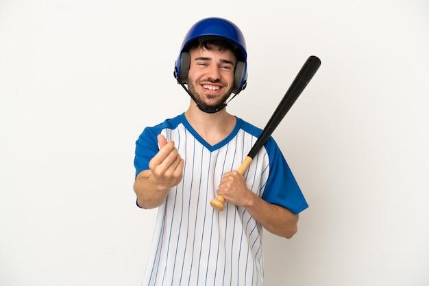 Jovem homem caucasiano jogando beisebol isolado no fundo branco fazendo gesto de dinheiro