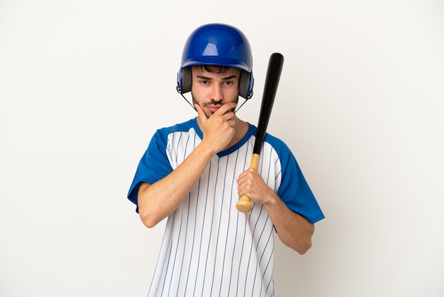 Jovem homem caucasiano jogando beisebol isolado no fundo branco pensando