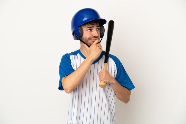 Jovem homem caucasiano jogando beisebol isolado no fundo branco, tendo dúvidas e pensando