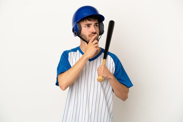 Jovem homem caucasiano jogando beisebol isolado no fundo branco, tendo dúvidas enquanto olha para cima