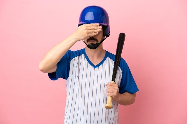 Jovem homem caucasiano jogando beisebol isolado no fundo rosa, cobrindo os olhos com as mãos. não quero ver nada