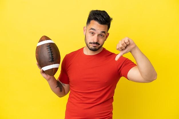 Jovem homem caucasiano jogando rúgbi isolado em fundo amarelo, mostrando o polegar para baixo com expressão negativa