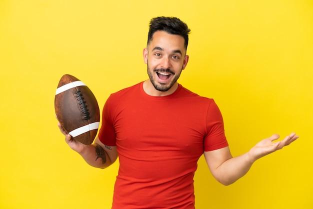 Jovem homem caucasiano jogando rúgbi isolado em um fundo amarelo com expressão facial chocada