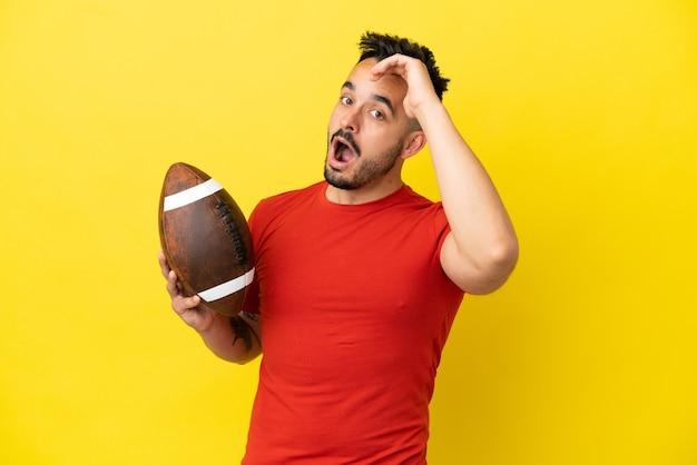 Jovem homem caucasiano jogando rúgbi isolado em um fundo amarelo fazendo gesto surpresa enquanto olha para o lado