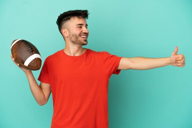 Jovem homem caucasiano jogando rúgbi isolado em um fundo azul fazendo um gesto de polegar para cima