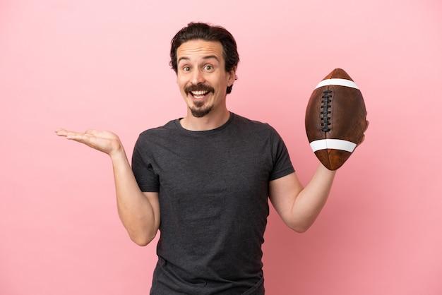 Jovem homem caucasiano jogando rúgbi isolado em um fundo rosa com expressão facial chocada