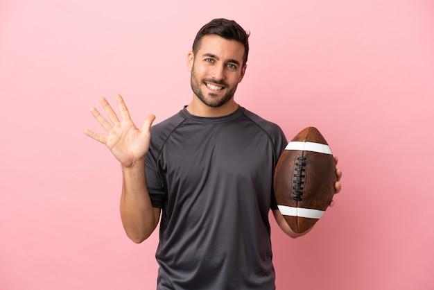 Jovem homem caucasiano jogando rúgbi isolado em um fundo rosa contando cinco com os dedos