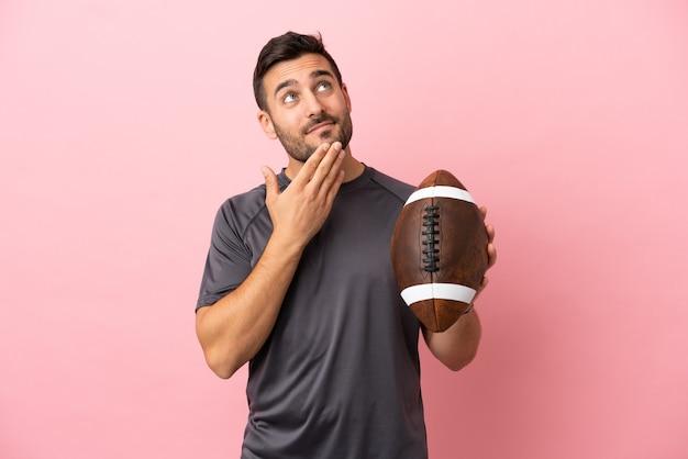 Jovem homem caucasiano jogando rúgbi isolado em um fundo rosa, olhando para cima enquanto sorri