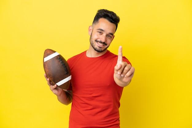 Jovem homem caucasiano jogando rugby isolado em um fundo amarelo, mostrando e levantando um dedo