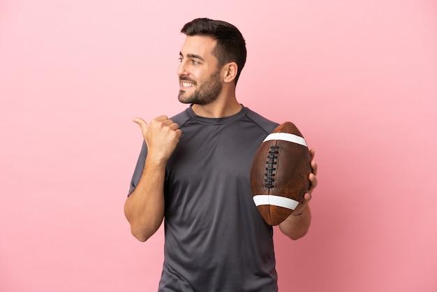 Jovem homem caucasiano jogando rugby isolado em um fundo rosa apontando para o lado para apresentar um produto